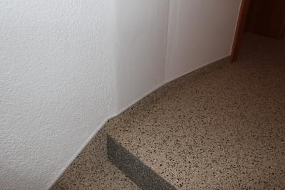 Steinteppich_Natursteinteppich_beiger_Boden_Stiege_SeitlicherWandabschluss-Detailaufnahme