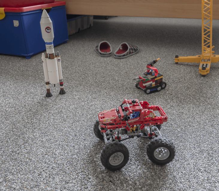 Steinteppich_Natursteinteppich_grauer_Boden_Kinderspielzeug_Kran_Autos_Rakete